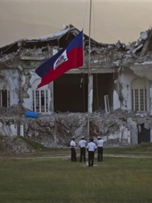 Police lower the national flag in front of the damaged presidential palace on the first...