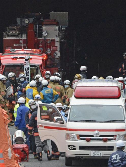Police officers and firefighters gather in front of the Sasago Tunnel on the Chuo Expressway in...