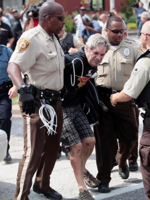 Police officers detain a demonstrator for protesting Michael Brown's murder in Ferguson, Missouri...