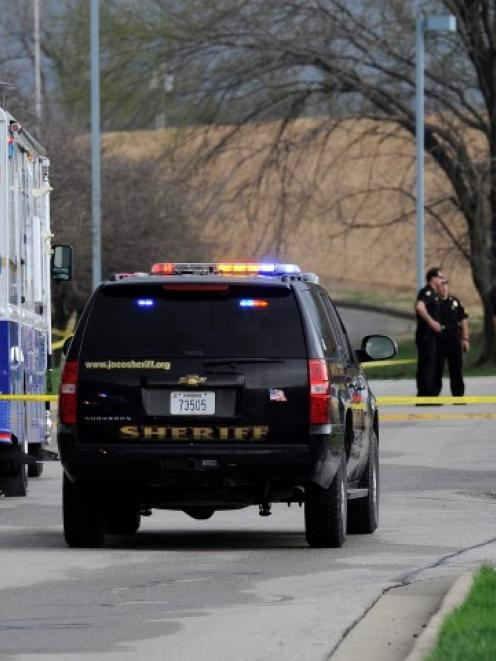 Police officers gather at the scene of a shooting at the Jewish Community Center of Greater...