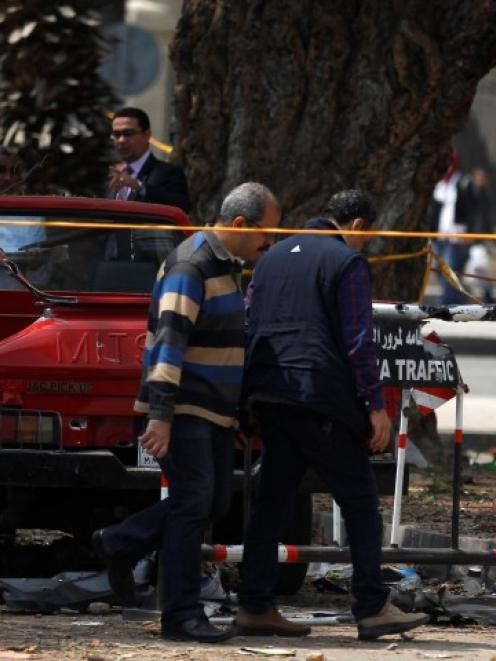 Police officers inspect near the site of the explosions in front of Cairo University. REUTERS/Amr...