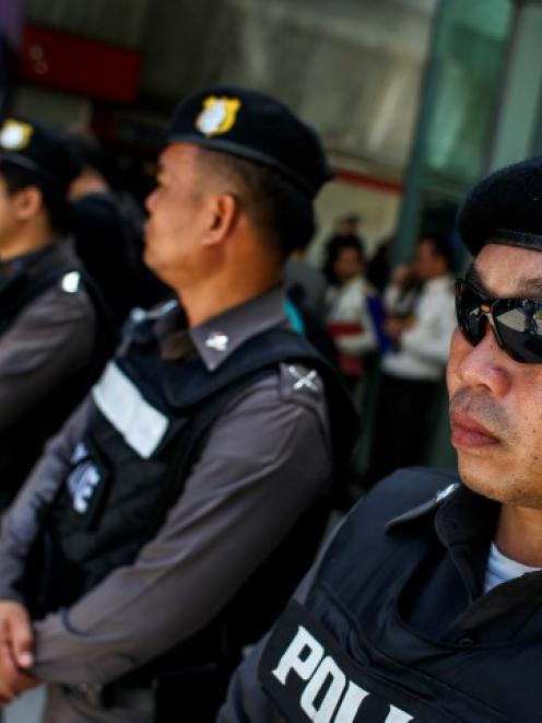 Police officers stand guard at a shopping mall in Bangkok. REUTERS/Athit Perawongmetha