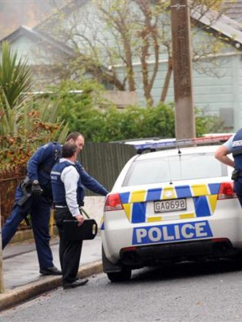 Police remove items from a Malvern St address yesterday morning.  Photo by staff photographer.