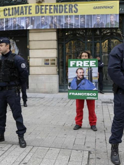 Police secure the area as Greenpeace activists protest in front of Gazprom headquarters in Paris....