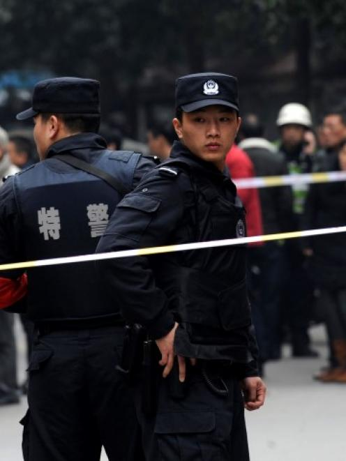 Police stand guard at a crime scene after a deadly knifing incident in Changsha, Hunan province,...