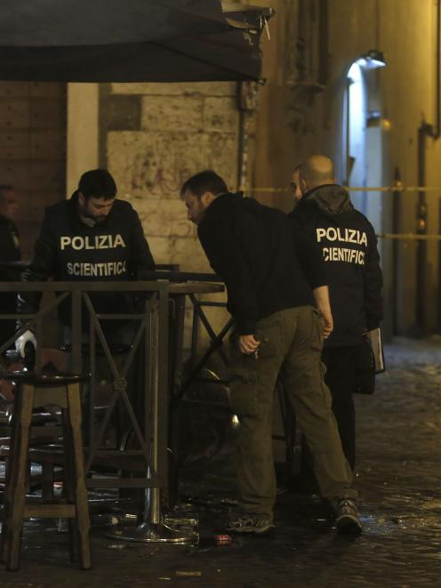 Policemen inspect a damaged pub in Rome after 10 supporters of English soccer club Tottenham ...