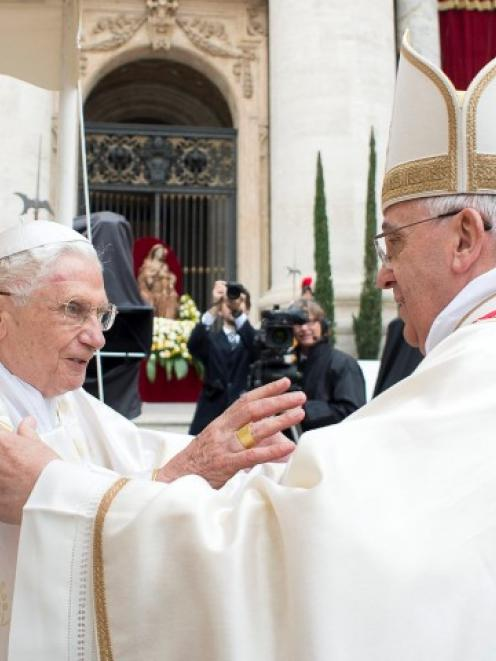 Pope Francis (R) embraces Pope Emeritus Benedict XVI during Mass before the canonisation ceremony...