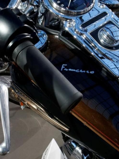 Pope Francis' signature is seen on the tank of his Harley Davidson Dyna Super Glide before its...