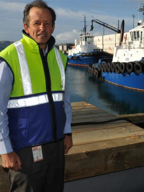 Port Otago's Geoff Plunket in front of the Ports tug Otago. Photo by ODT.
