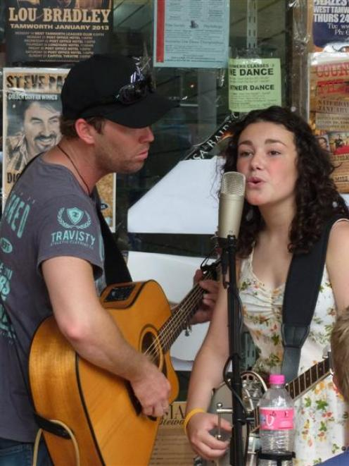 Postal band member Jason Grice,  of Sydney, and Gore's Jenny Mitchell (13) busk at the Tamworth...
