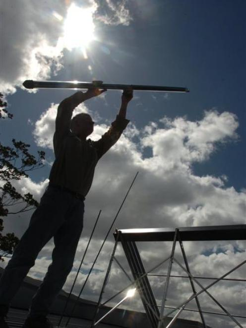 Power Options director Ian Buchan installs a solar water heating system at a Maori Hill property...