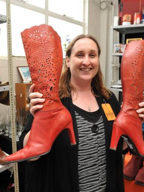 Presbyterian Support Otago retail assistant Donna Knox holds some red size-10 boots in the annual...
