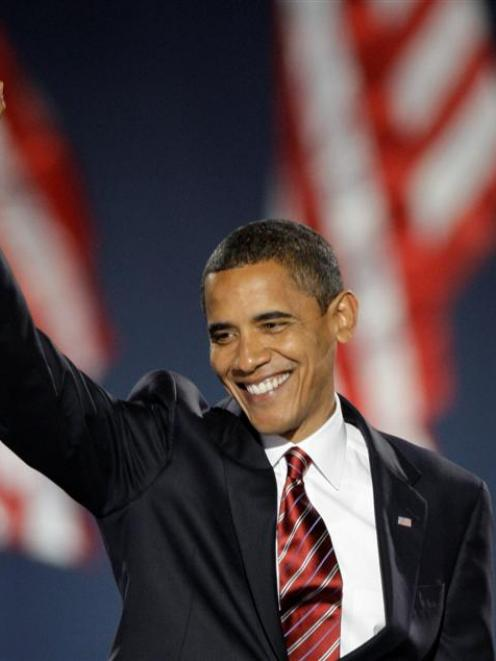 President-elect Barack Obama waves as he takes the stage at his election night party in Chicago's...