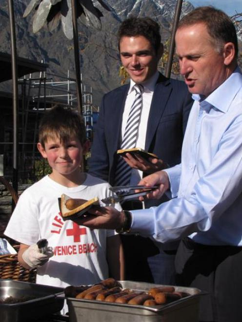 Prime Minister John Key hands out free sausages at Remarkables Park Town Centre yesterday with...