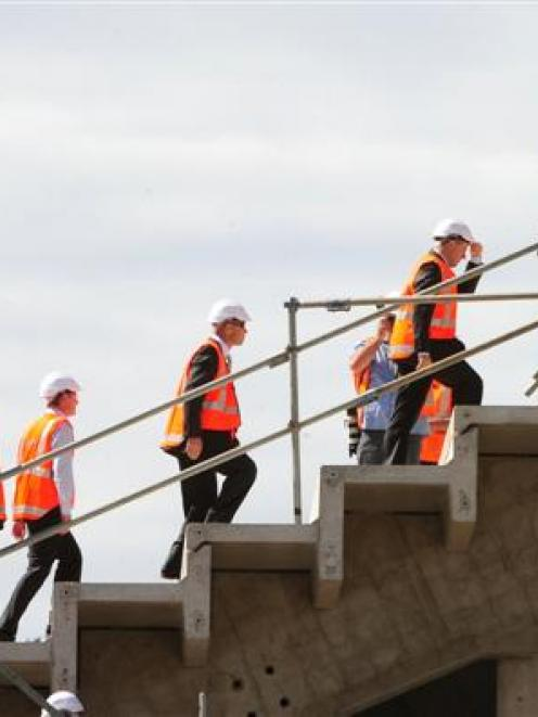 Prime Minister John Key (holding the peak of his hard hat) climbs to the top of the Forsyth Barr...