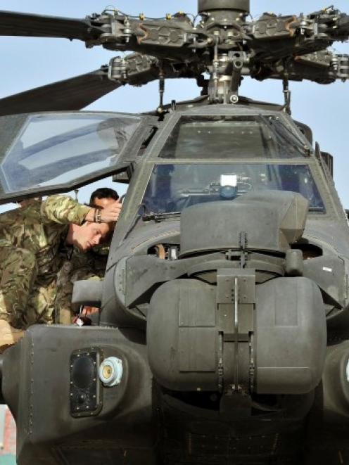 Prince Harry climbs up to examine the cockpit of an Apache helicopter at Camp Bastion in...