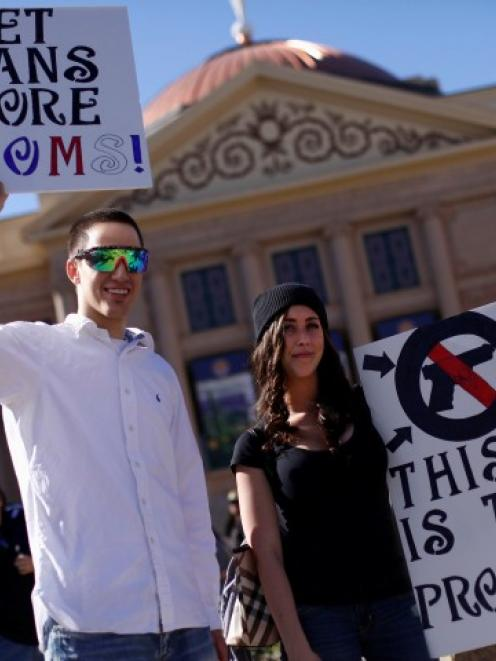 Pro-gun demonstrators take part in a 'high noon' rally outside the Arizona State Capitol in...