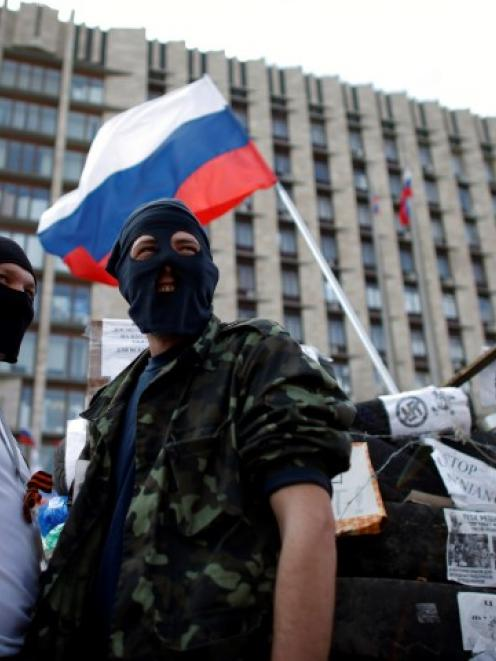 Pro-Russia protesters stand guard near a barricade outside a regional government building in...