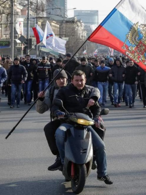 Pro-Russian demonstrators ride on a motorcycle as they take part in a rally in Donetsk, Ukraine....