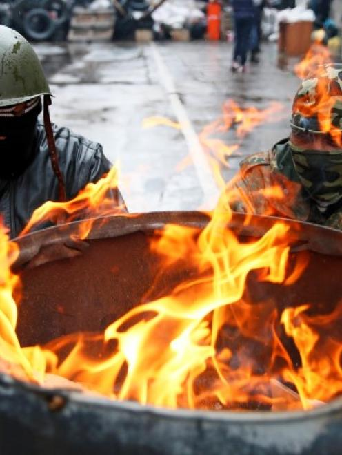Pro-Russian men gather around a fire at a barricade near the police headquarters in Slaviansk,...
