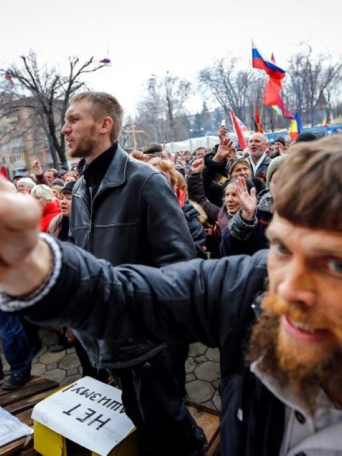 Pro-Russian protesters attend a rally in front of the seized office of the SBU state security...