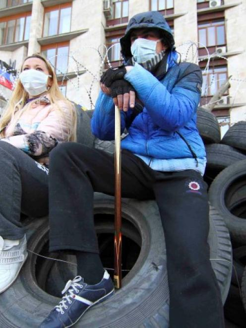 Pro-Russian protesters sit on automobile tyres outside a regional government building in Donetsk....