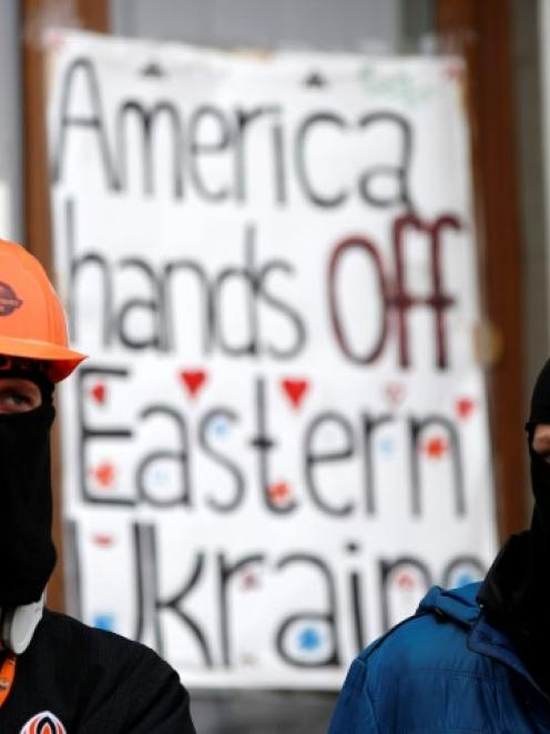 Pro-Russian protesters stand guard outside a regional government building in Donetsk, eastern...