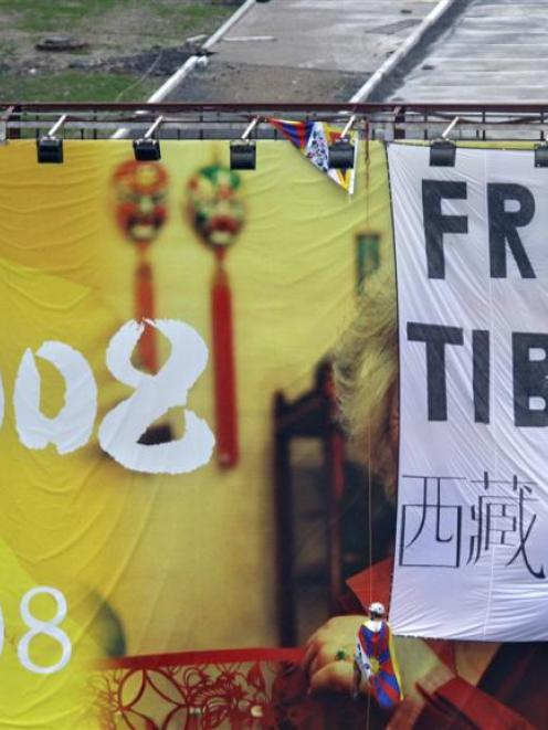 "Pro Tibet activists unfurl a ""Free Tibet"" banner and Tibetan flags on top of a Beijing Olympics..."