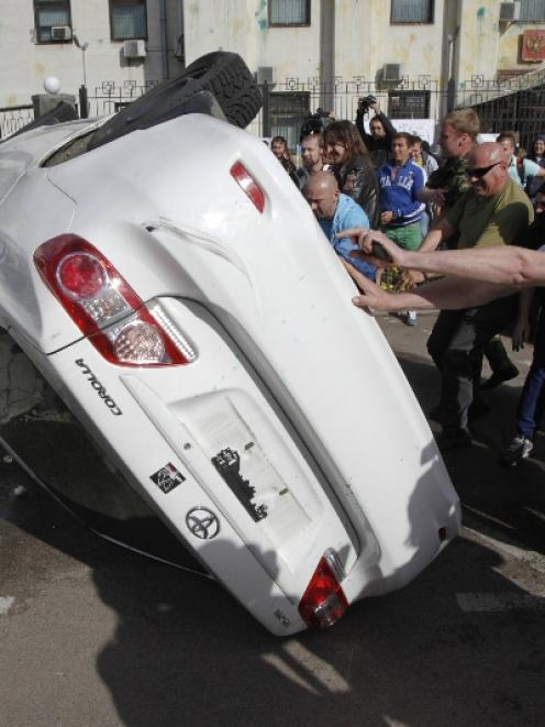 Pro-Ukrainian people overturn a car during a rally in front of the Russian embassy in Kiev. Photo...