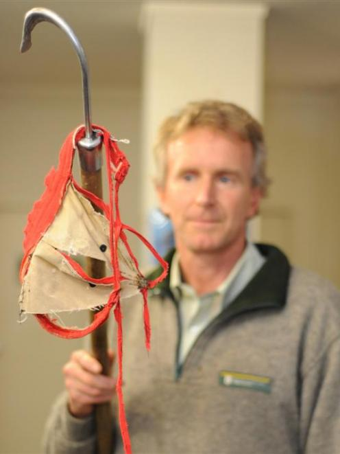 Profile ... Department of Conservation marine ranger Jim Fyfe with the item he removed from a...