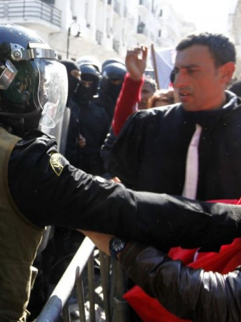 Protesters clash with riot police during a demonstration after the death of Tunisian opposition...