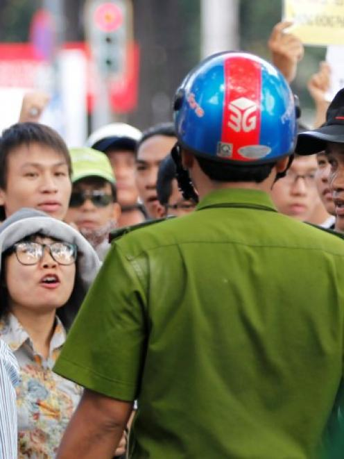 Protesters confront a policeman as they march during an anti-China protest in Vietnam's southern...
