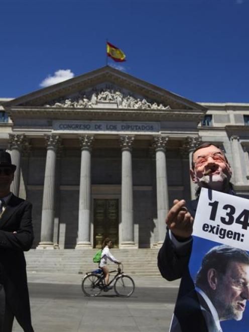 Protesters portraying a bailed-out banker (left) and Spanish Prime Minister Mariano Rajoy...