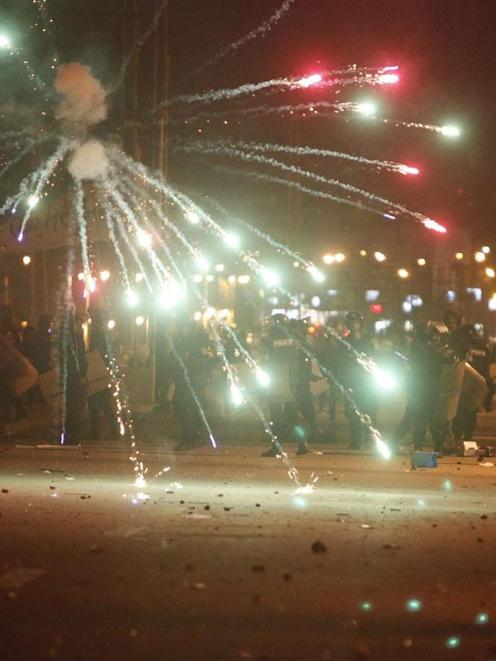 Protesters throw fireworks on police in front of the presidential palace, in Cairo. REUTERS/Asmaa...