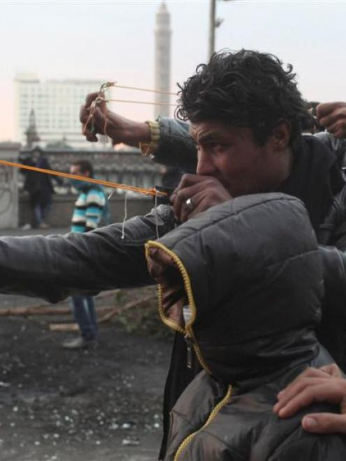 Protesters use slingshots to launch stones at riot police during clashes near Qasr el-Nil bridge,...