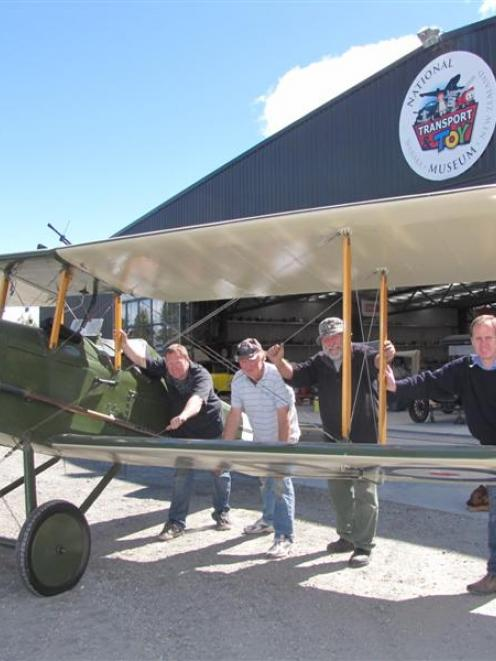Pushing a 1970 replica SE5A plane out of a hangar at Wanaka's National Transport and Toy Museum...