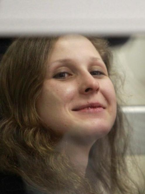 Pussy Riot member Maria Alyokhina looks out from a defendants' box during a court hearing in...