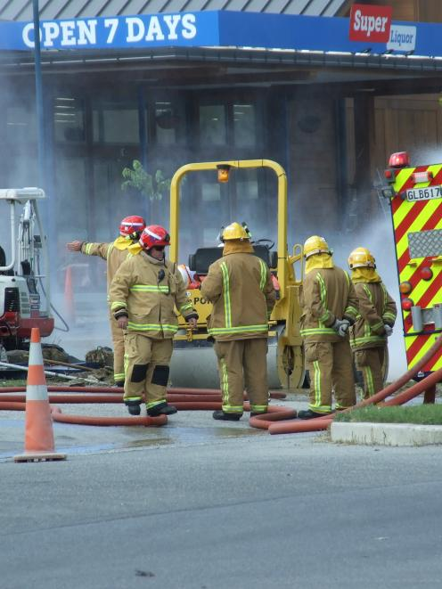 Firefighters douse a gas pipe damaged by a digger in Frankton yesterday afternoon. Photo by Guy...