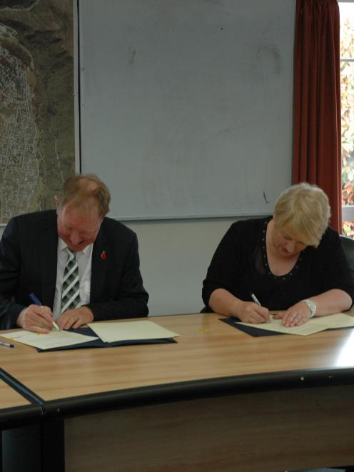 Housing Minister Nick Smith and Queenstown Lakes Mayor Vanessa van Uden sign the agreement...