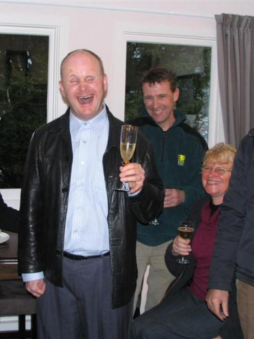 Queenstown pianist Mark Wilson toasts those who renovated his home. They included (from left)...