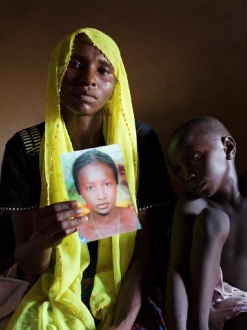 Rachel Daniel holds up a picture of her abducted daughter Rose Daniel as her son Bukar sits...