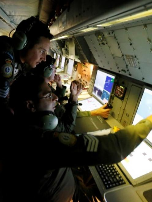 Radar specialists on board a Royal New Zealand Air Force P-3K2 Orion take part in the search for...