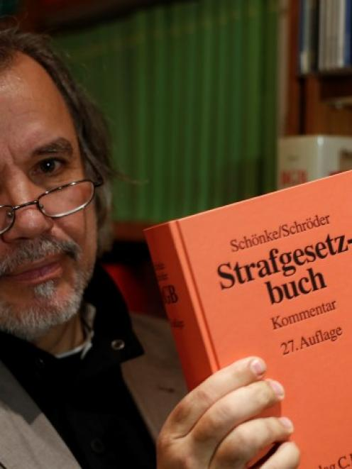 Rainer Pohlen, the lawyer for the former SS soldier, poses with an edition of Germany's Criminal...