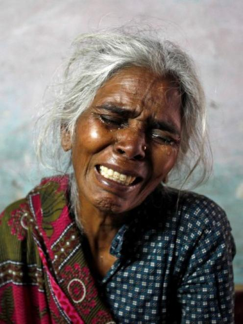 Ram Bai, mother of Ram Singh, wails inside her house at Ravi Das camp in New Delhi after her son...