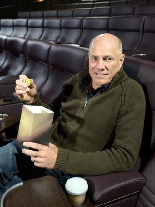 Reading Entertainment managing director Wayne Smith, of Melbourne, eats popcorn in the new...