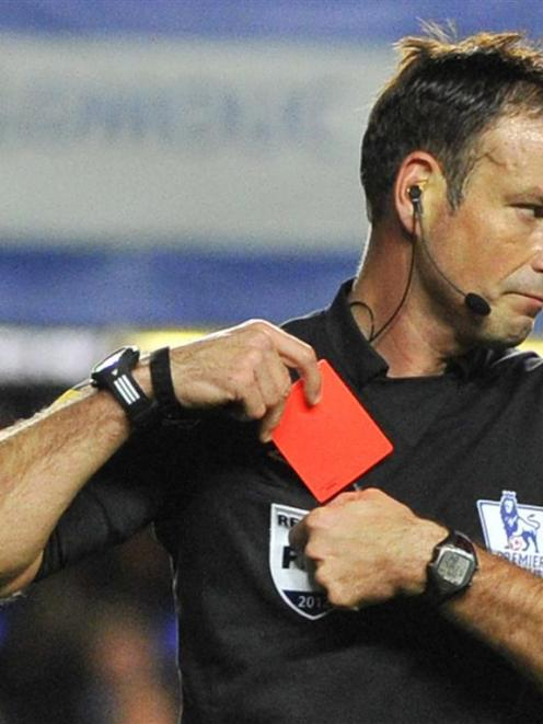 Referee Mark Clattenburg holds a red card after sending off Chelsea's Branislav Ivanovic during...