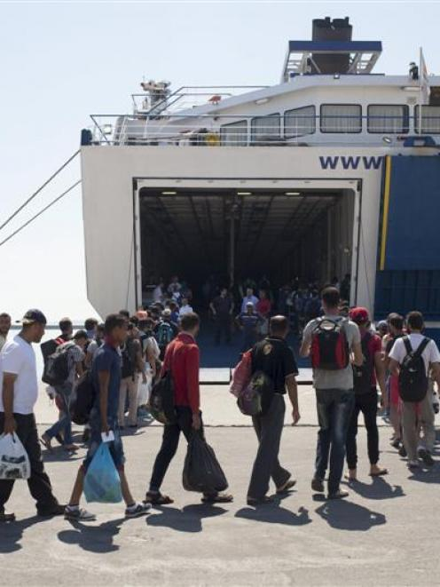 Refugees and migrants line up while boarding  a passenger ship heading to the Greek port of...