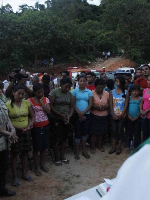 Relatives and friends of eight miners trapped in a gold mine affected by a landslide pray during...