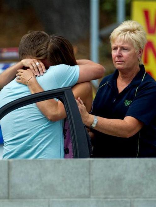Relatives of a man who was attacked and killed by a shark at Muriwai Beach yesterday hug while...