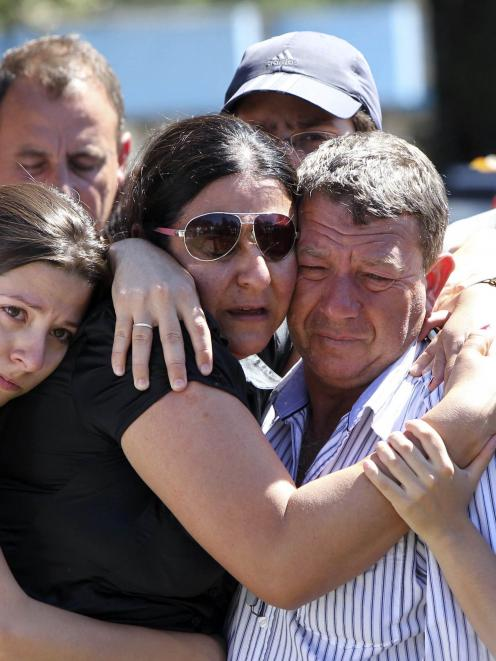 Relatives of Carlos Alexandre Machado, one of the victims of a fire at Boate Kiss nightclub,...